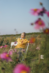 Young woman relaxing in cottage gardenの写真素材 [FYI04345291]