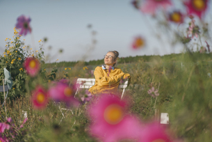 Young woman relaxing in cottage gardenの写真素材 [FYI04345292]