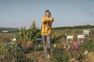 Smiling young woman with spade in cottage gardenの写真素材 [FYI04345294]