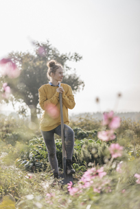 Young woman with spade in cottage gardenの写真素材 [FYI04345298]