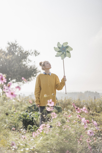Young woman with pinwheel in cottage gardenの写真素材 [FYI04345303]