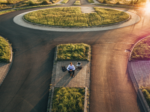 Businessman with laptop sitting on traffic island in roundabの写真素材 [FYI04345354]