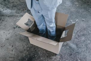 Businessman standing inside cardboard boxの写真素材 [FYI04345384]