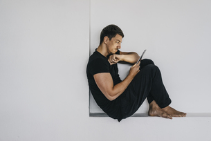 Man sitting in niche using tabletの写真素材 [FYI04345394]