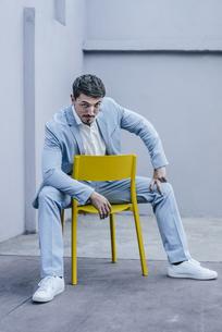 Portrait of confident businessman sitting on yellow chairの写真素材 [FYI04345400]