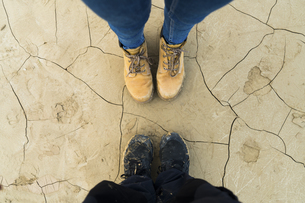 Feet of a couple standing on dried cracked groundの写真素材 [FYI04345411]
