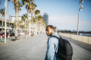 Spain, Barcelona, young man with backpack walking on beach pの写真素材 [FYI04345419]
