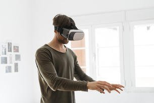 Young man wearing virtual reality glasses at homeの写真素材 [FYI04345426]
