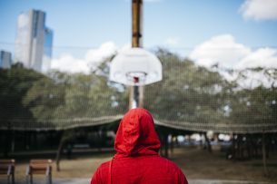 Young man wearing red hoodie on a basketball courtの写真素材 [FYI04345434]