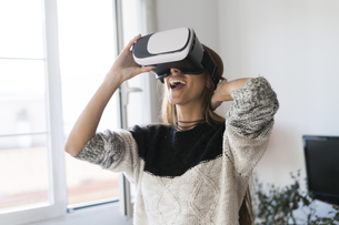 Excited young woman wearing VR glasses at homeの写真素材 [FYI04345440]
