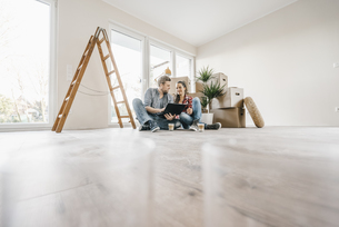 Couple sitting on floor of their new home among moving boxesの写真素材 [FYI04345466]