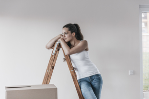 Mature woman standing in her new home, leaning on ladderの写真素材 [FYI04345472]