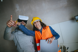 Woman on construction site showing a man with virtual realitの写真素材 [FYI04345477]
