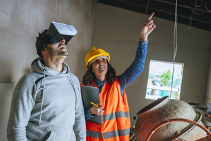 Woman on construction site showing a man with virtual realitの写真素材 [FYI04345478]