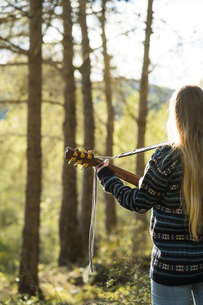 Young woman playing guitar in natureの写真素材 [FYI04345480]
