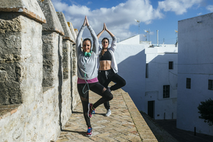 Two young women exercising yoga in the streetの写真素材 [FYI04345486]