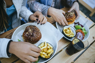 Women's hands eating Hamburgers and French friesの写真素材 [FYI04345505]