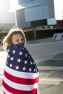 Spain, Barcelona, portrait of young woman wrapped in US Amerの写真素材 [FYI04345532]