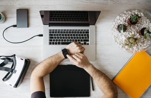 Man using smartwatch at desk, top viewの写真素材 [FYI04345636]