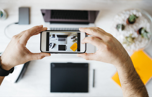 Man taking a photo of his desktop with smartphone, top viewの写真素材 [FYI04345637]