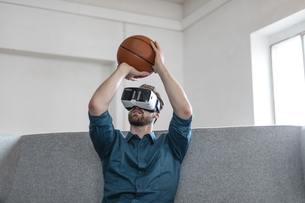 Young man with basketball sitting on couch using Virtual Reaの写真素材 [FYI04345667]