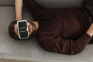 Man lying on the couch using Virtual Reality Glassesの写真素材 [FYI04345674]