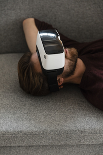 Man lying on the couch using Virtual Reality Glassesの写真素材 [FYI04345676]