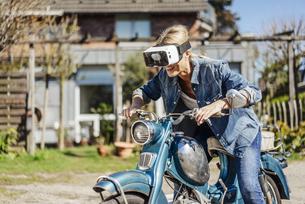 Happy woman on vintage motorcycle wearing VR glassesの写真素材 [FYI04345690]