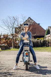 Woman sitting backwards on vintage motorcycle wearing VR glaの写真素材 [FYI04345693]