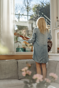 Woman at home standing on couch looking out of windowの写真素材 [FYI04345694]