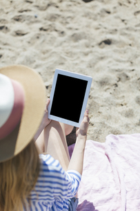 Woman sitting on the beach with tabletの写真素材 [FYI04345703]