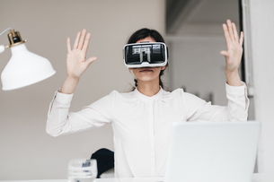 Businesswoman wearing VR glasses in officeの写真素材 [FYI04345710]