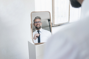 Businessman looking into mirror, fastening his tieの写真素材 [FYI04345755]