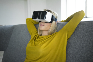 Woman sitting on couch wearing virtual reality glassesの写真素材 [FYI04345758]