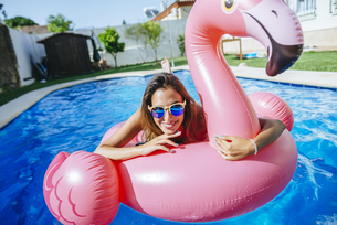 Portrait of happy young woman with pink flamingo float in swの写真素材 [FYI04345766]