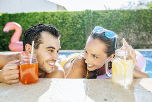 Happy couple in swimming pool with drinks at the poolsideの写真素材 [FYI04345767]
