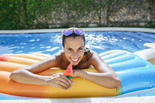 Portrait of happy young woman on airbed in swimming poolの写真素材 [FYI04345770]