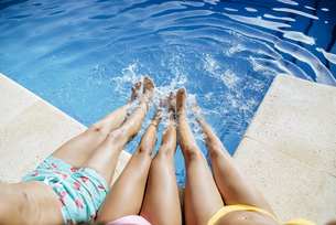 Legs of friends splashing in poolの写真素材 [FYI04345773]