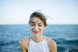 Young woman smiling with eyes closed with sea backgroundの写真素材 [FYI04345796]