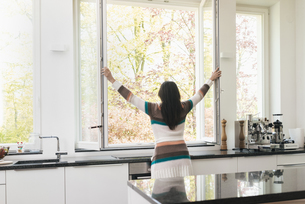 Woman in kitchen opening the windowの写真素材 [FYI04345799]