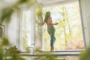 Woman standing in kitchen on windowsillの写真素材 [FYI04345802]