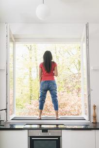 Woman standing in kitchen on windowsillの写真素材 [FYI04345804]