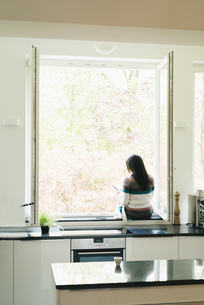 Woman in kitchen sitting on windowsillの写真素材 [FYI04345809]