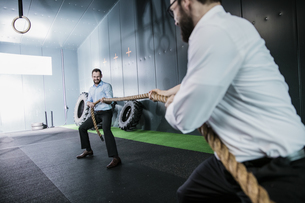 Two businessmen in gym doing tug of warの写真素材 [FYI04345812]