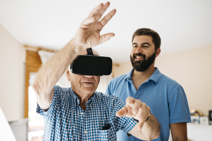Senior man using Virtual Reality Glasses at home while his aの写真素材 [FYI04345813]