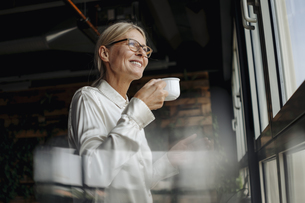 Smiling businesswomanholding cup of coffee looking out of wiの写真素材 [FYI04345816]