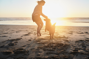 Portugal, Algarve, woman with dog on the beach at sunsetの写真素材 [FYI04345822]