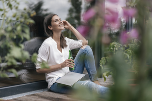 Happy woman with laptop and bottle sitting on balconyの写真素材 [FYI04345834]
