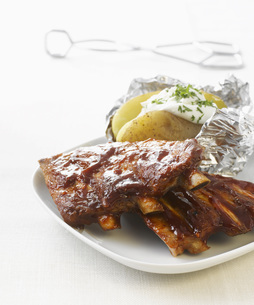 Barbecued Ribs with Baked potato on plateの写真素材 [FYI04345875]
