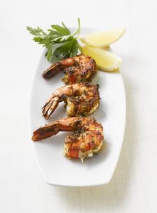 Grilled shrimps, parsley and lemon slices on platter, elevatの写真素材 [FYI04345877]